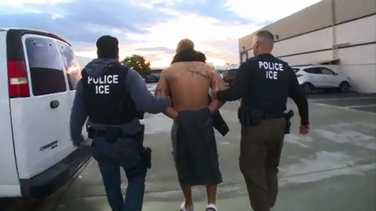 Two ICE officers arrest an undocumented immigrant during a raid in Orange County in March 2015.