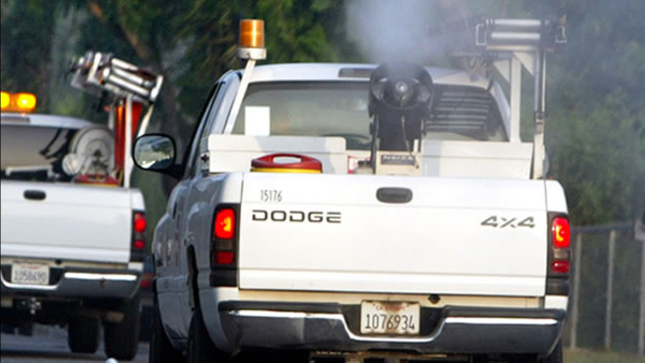 A truck from San Bernardino County Vector Control sprays pesticide to combat mosquitoes in Fontana, Calif., in this June 25, 2004, file photo.