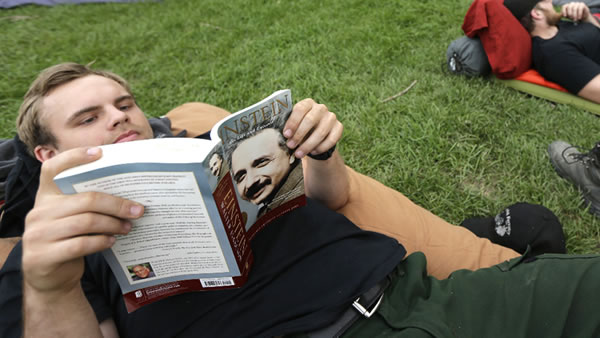 Zach Knudsen, left, reads a book about the life of Albert Einstein in Okanogan, Wash., Tuesday, Aug. 25, 2015.