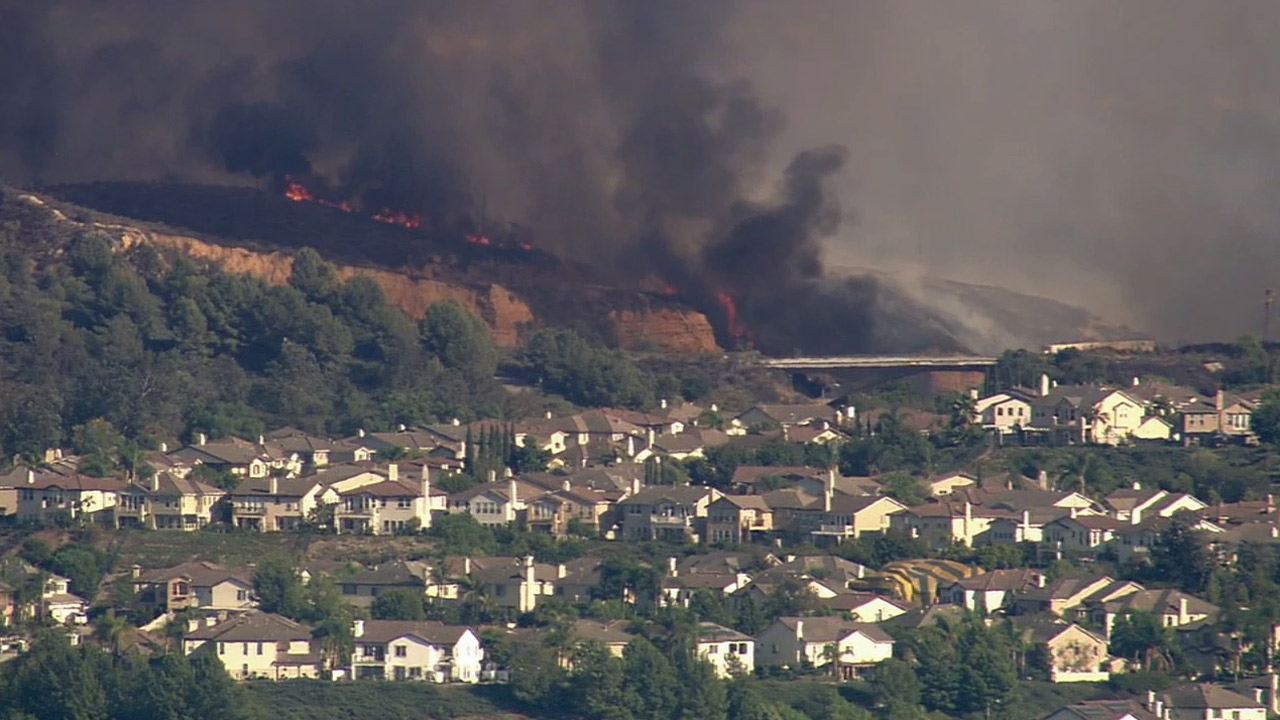 Flames and smoke erupt on a hillside near a gated community in La Habra by the Fullerton border on Tuesday, Sept. 8, 2015.