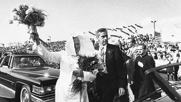 """<div class=""""meta image-caption""""><div class=""""origin-logo origin-image ap""""><span>AP</span></div><span class=""""caption-text"""">Pope John Paul II escorted by a Secret Service agent, waves a bouquet of flowers and holds another after arriving at Philadelphia International Airport, Oct. 3, 1979.</span></div>"""