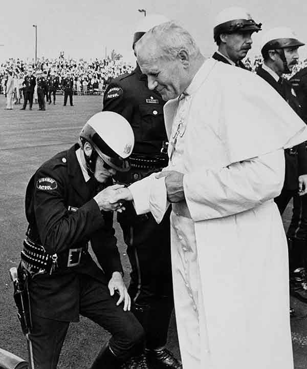 """<div class=""""meta image-caption""""><div class=""""origin-logo origin-image ap""""><span>AP</span></div><span class=""""caption-text"""">A Pennsylvania Highway patrolman kisses the hand of Pope John Paul II as he prepares to leave for Des Moines, Iowa, from the airport in Philadelphia,</span></div>"""