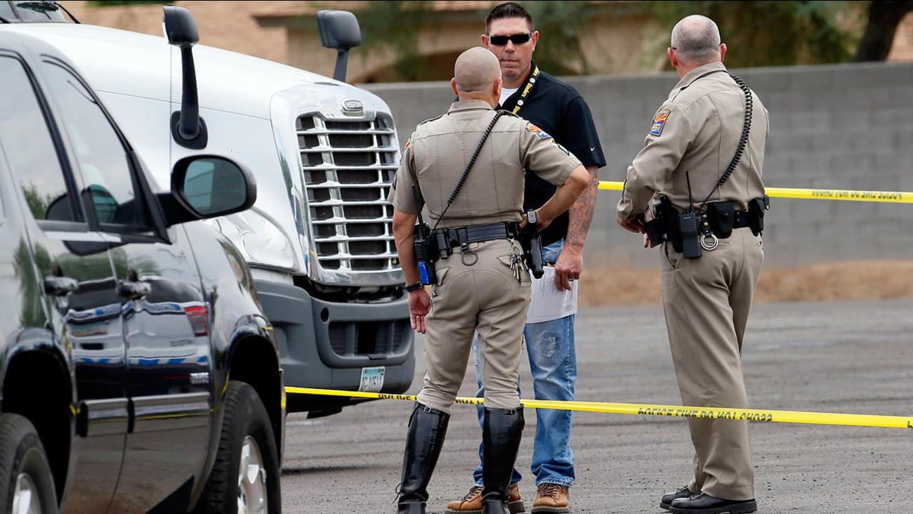 Arizona Department of Public Safety officers stand near a tractor trailer shortly after it was shot near 67th Ave and I-10, Thursday, Sept. 10, 2015 in Phoenix