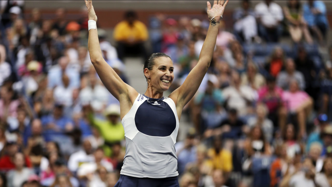 Italy's Flavia Pennetta tosses up her racket upon beating Roberta Vinci, of Italy, during the women's championship match of the U.S. Open on Saturday, Sept. 12, 2015, in New York.