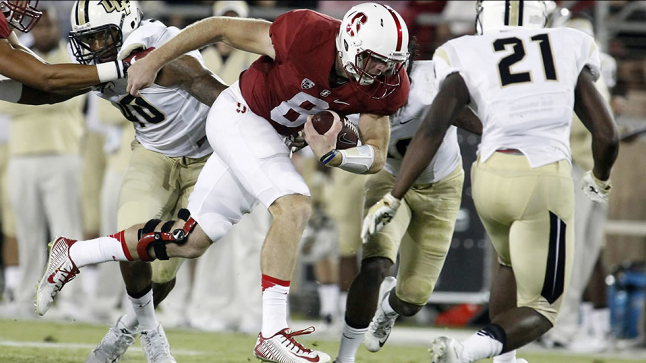 Stanford University quarterback Kevin Hogan runs the ball as UCF's Drico Johnson closes during an NCAA college football game Saturday, Sept. 12, 2015, in Stanford, Calif.