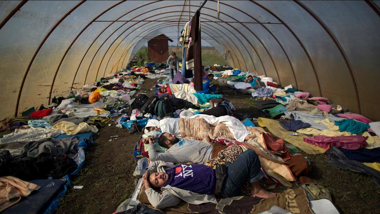 Syrian people sleep inside a greenhouse at a makeshift camp for asylum seekers near Roszke, southern Hungary, Sunday, Sept. 13, 2015.