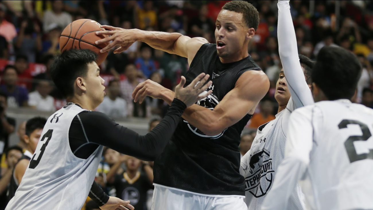 Warriors' Steph Curry makes a blind pass to a teammate during a basketball game with fans Saturday, Sept. 5, 2015 at Makati city east of Manila, Philippines. (AP Photo)