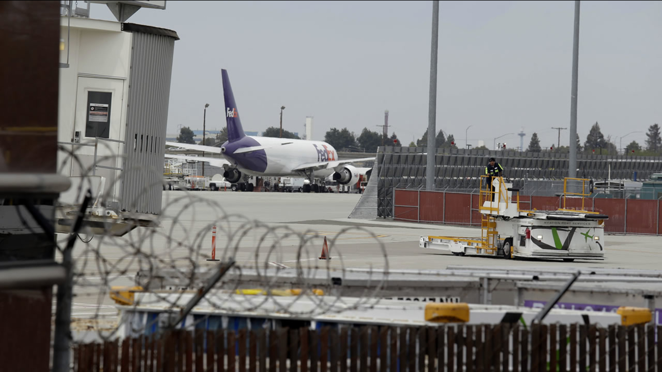 A worker moves equipment near gates used by Hawaiian Airlines at Terminal A of Mineta San Jose International Airport, Monday, April 21, 2014. (AP Photo/Eric Risberg)