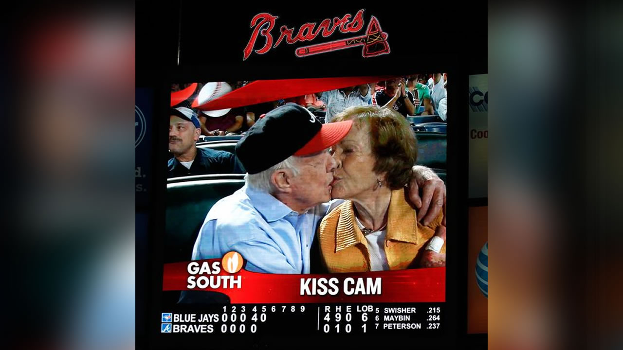 "Former President Jimmy Carter smooching with wife Rosalynn on the Atlanta Braves ""Kiss Cam""."