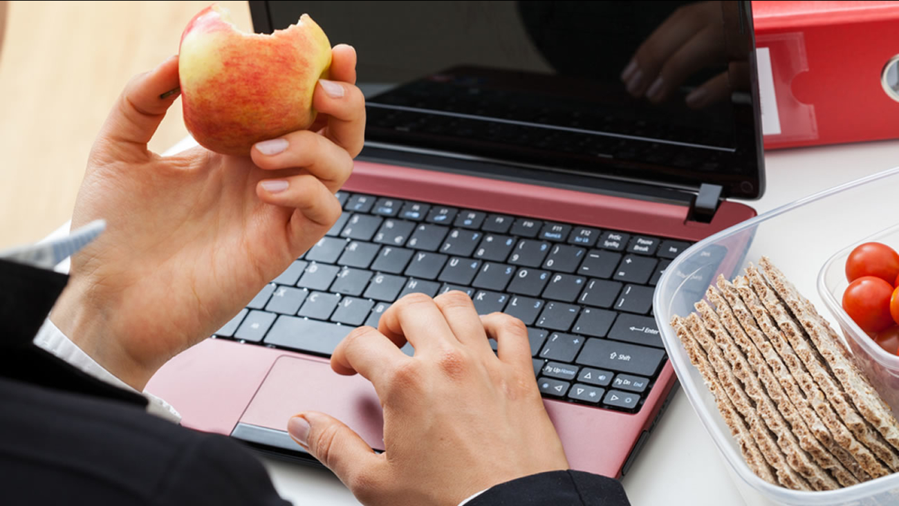 Person eats snacks while on his laptop