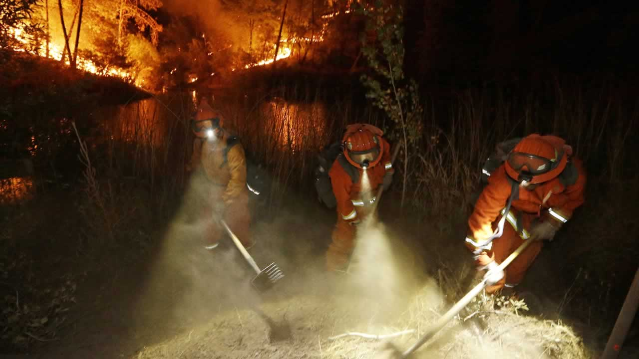 Firefighters create a firebreak near a home in Middletown, Calif., on Sunday, Sept. 13, 2015.