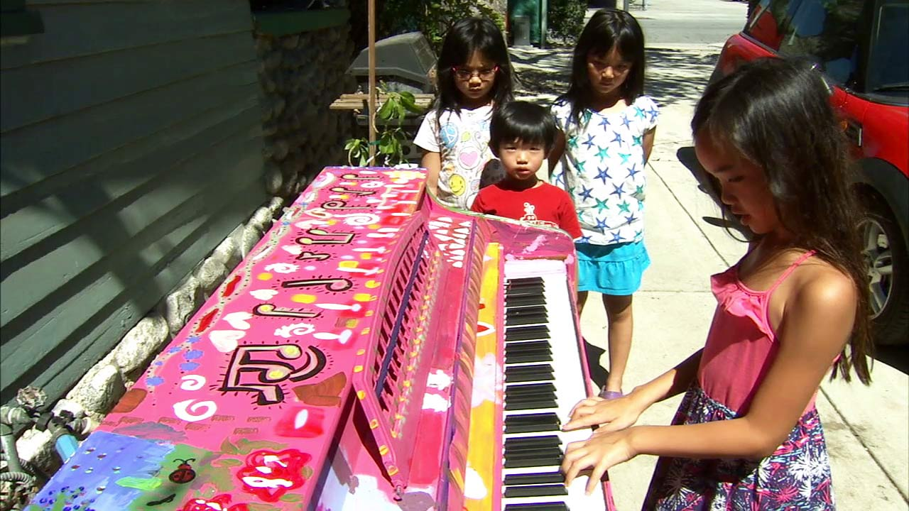 A child plays a colorful streetside piano outside of a Pasadena music studio.