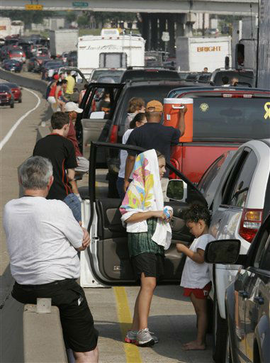 <div class='meta'><div class='origin-logo' data-origin='none'></div><span class='caption-text' data-credit='AP Photo/ RON HEFLIN'>Hurricane evacuees stand by the side of their automobiles on Highway 290 leading out of Houston in this Sept. 22, 2005 file photo. (AP Photo/Ron Heflin)</span></div>