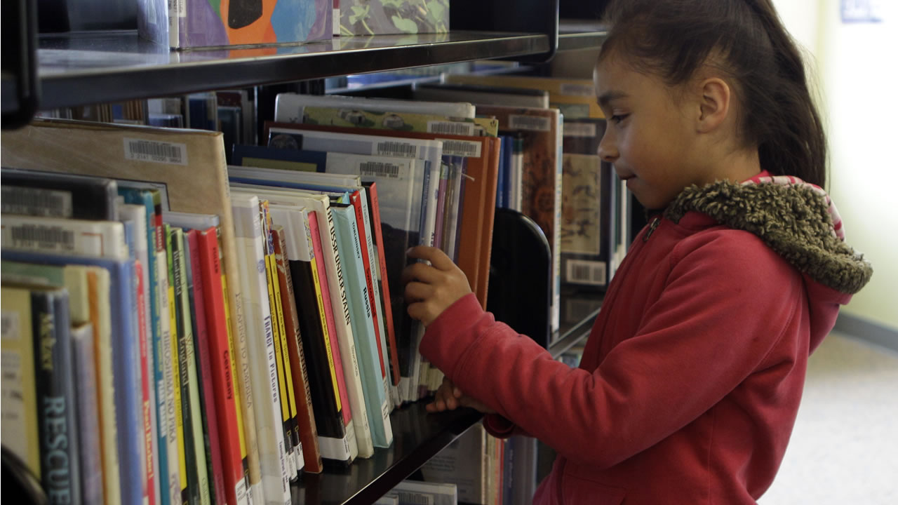 In this May 25, 2011 photo, Jennifer Rodriguez, 7, picks out a book to read after school at the Cesar Chavez Library in Oakland, Calif. (AP Photo/Ben Margot)