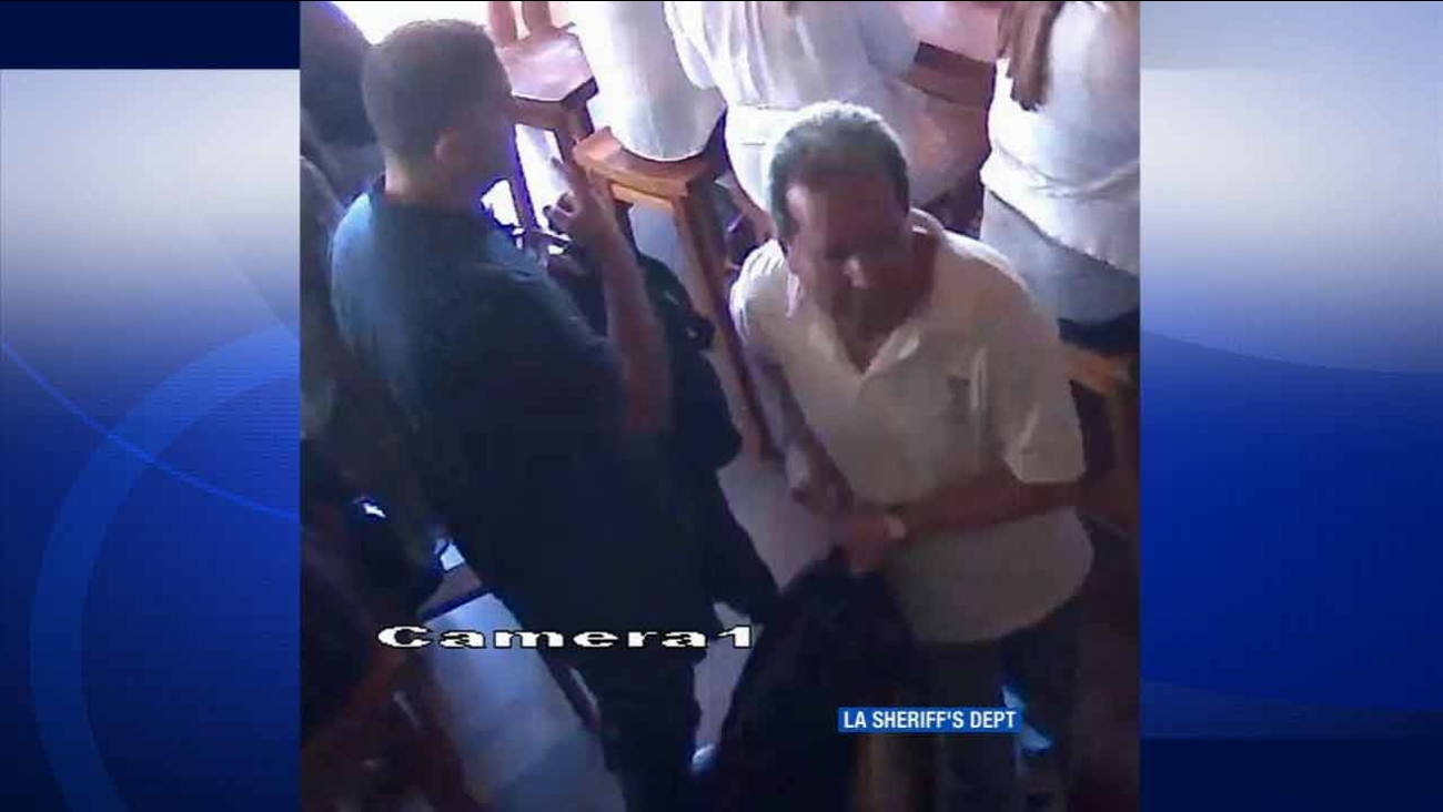 Two suspects caught on surveillance video are seen stealing a woman's purse from under a bar stool at a popular Malibu restaurant in August 2015.